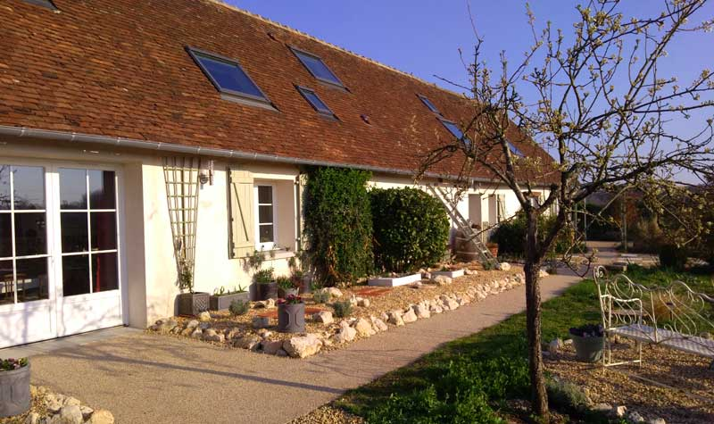 Long farm house style building in the Loire Valley with shutters and surrounded by a big garden