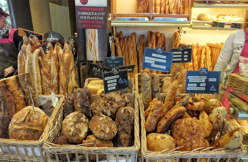 Several different kinds of bread in whicker baskets in an artisan bakery in France