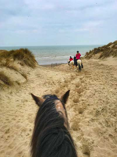 People riding horses in sand dunes leading to the sea in Le Touquet