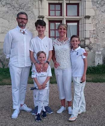 Man, woman and three boys dressed in white posing at their gite BnB in France