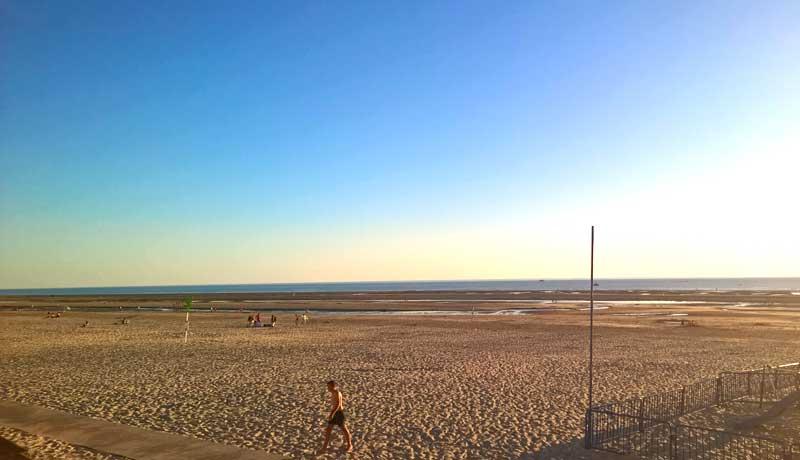Man walks on a pristine sandy beach as the sun sets in Le Touquet-Paris-Plage, northern France