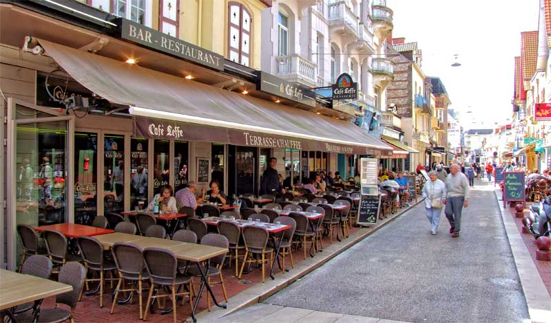Street lined with restaurants and bars, tables on pavements in Le Touquet France