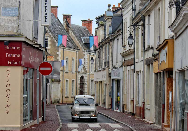 Old French car on a narrow road festooned with bunting and lined with old shops and houses
