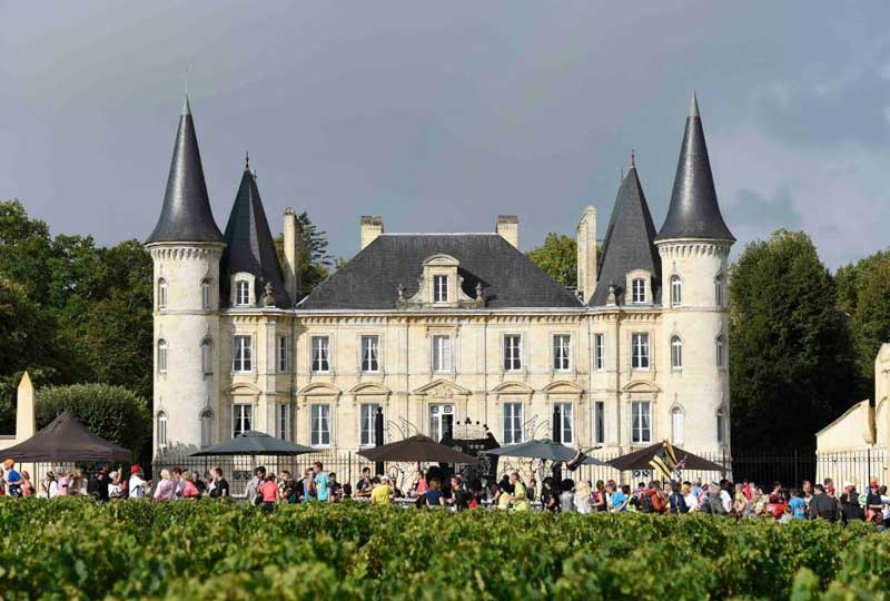 Castle surrounded by vineyards in Bordeaux with many marathon runners passing by