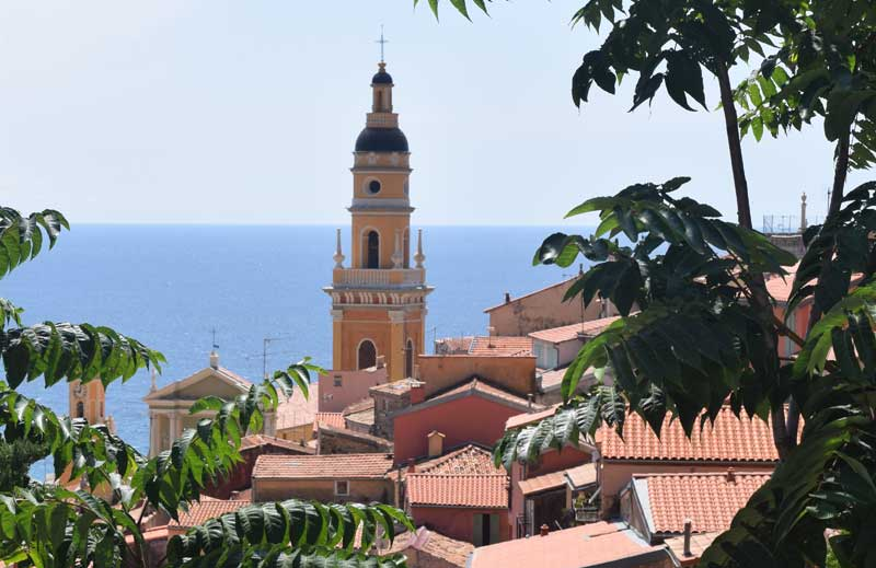 Pointed church tower reaching above terracotta roof tops, Mediterranean sea in the background at Menton, France