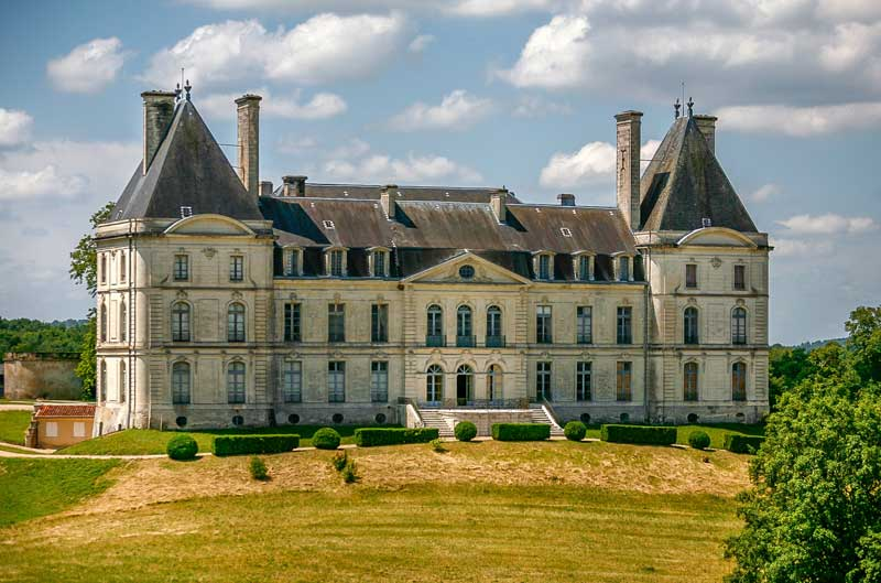 Large chateau in the French countryside, surrounded by vineyards and fields
