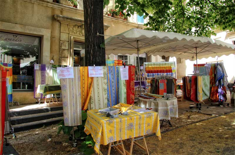 A market stall in Avignon Provence draped with colourful tablecloths