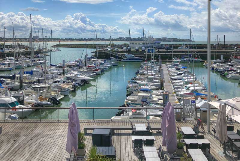 Sea front of Royan, boats in the harbour, boardwalk with tables and chairs of cafes and bars