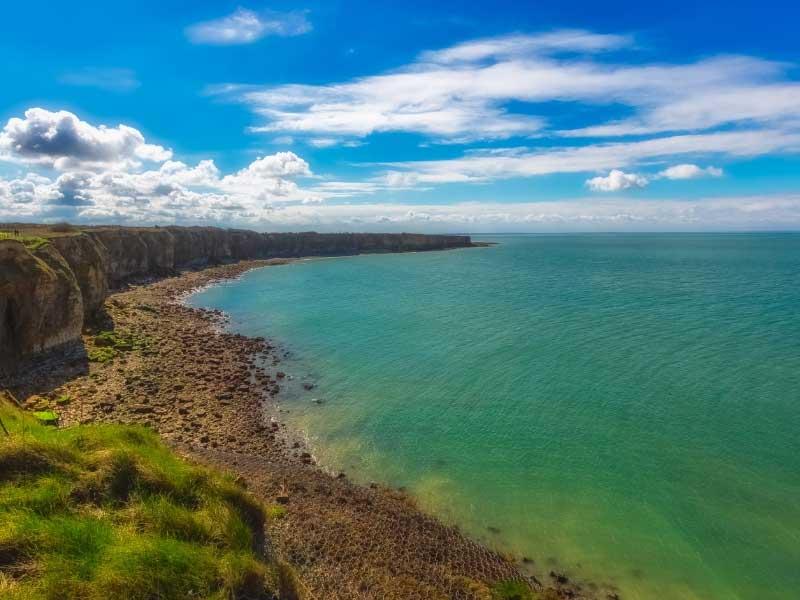 Aerial view of Utah Beach in Normandy, sunny sky, deep blue waters, sandy beach