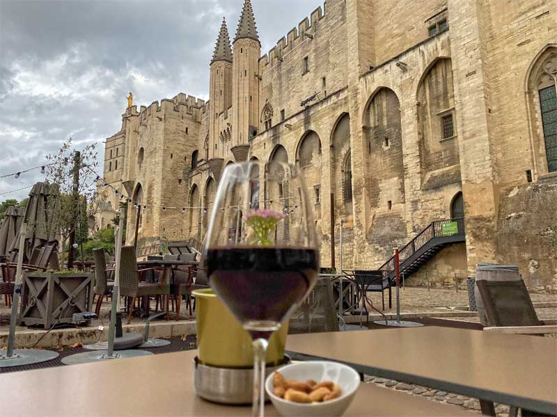Glass of red wine on a table in a square in front of the Palace of the Popes in Avignon on a stormy day