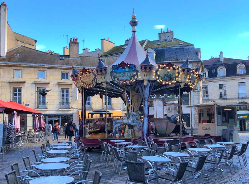 Carousel in a cobbled square in Dijon at dusk, surrounded by tables and chairs