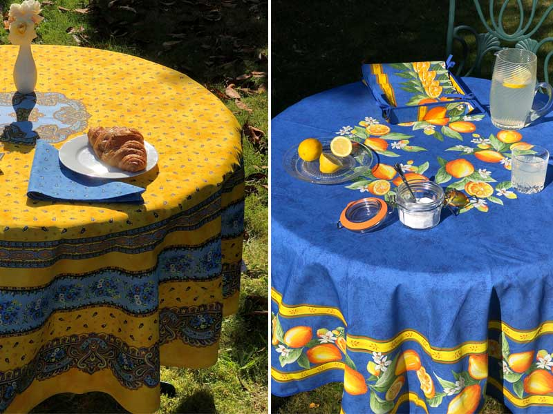 Round tables in a garden with bright tablecloths and set for breakfast with croissants and juice