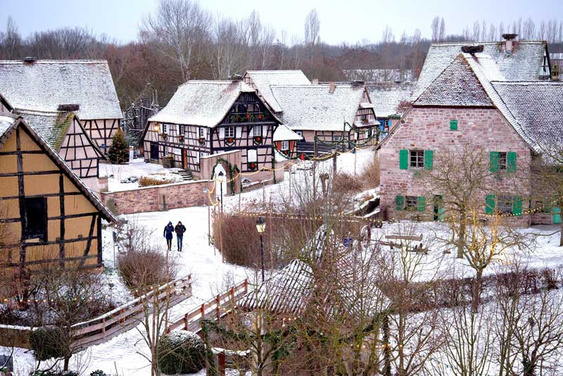 Pretty village of half-timbered houses decorated for Christmas at Mulhouse Eco Museum of Alsace