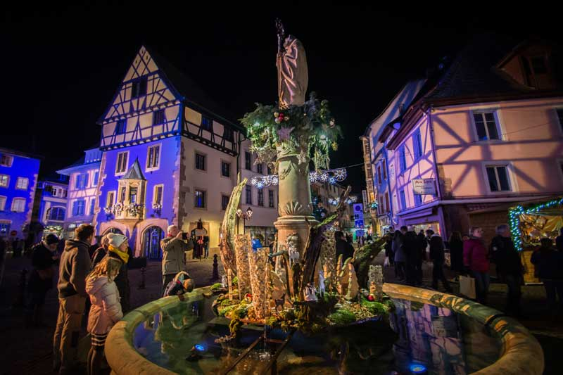 Fountain in the village of Thann near Mulhouse, lit up for Christmas