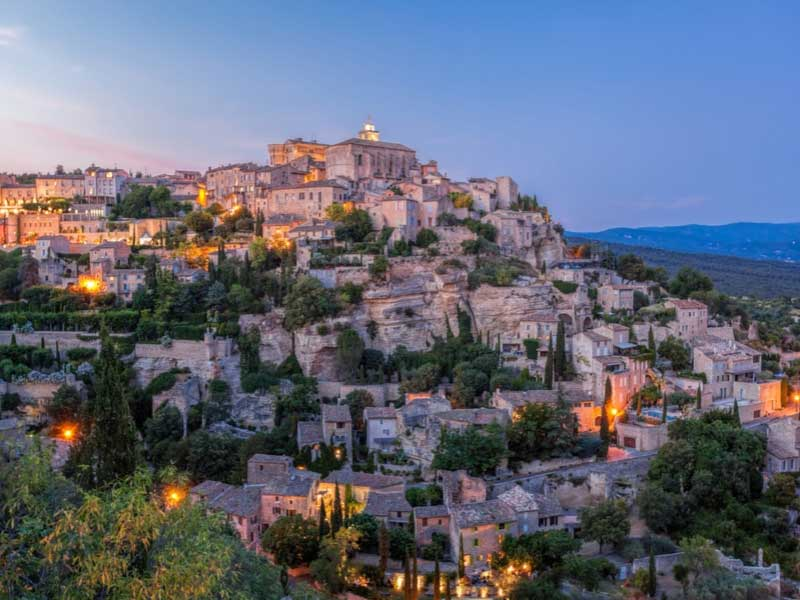 Hilltop town of Gordes in Provence, lit up just as dusk falls
