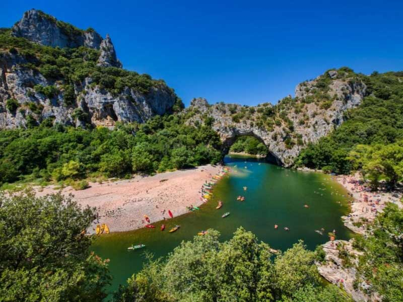 Canoes on the River Ardeche, clear blue green waters, a sunny day, surrounded by mountains
