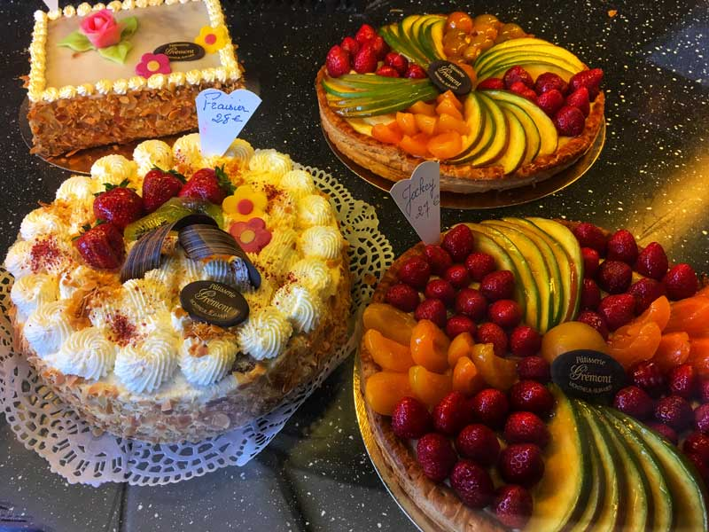 Scrumptious cakes topped with fruit, cream and icing at a bakery in Montreuil-sur-Mer