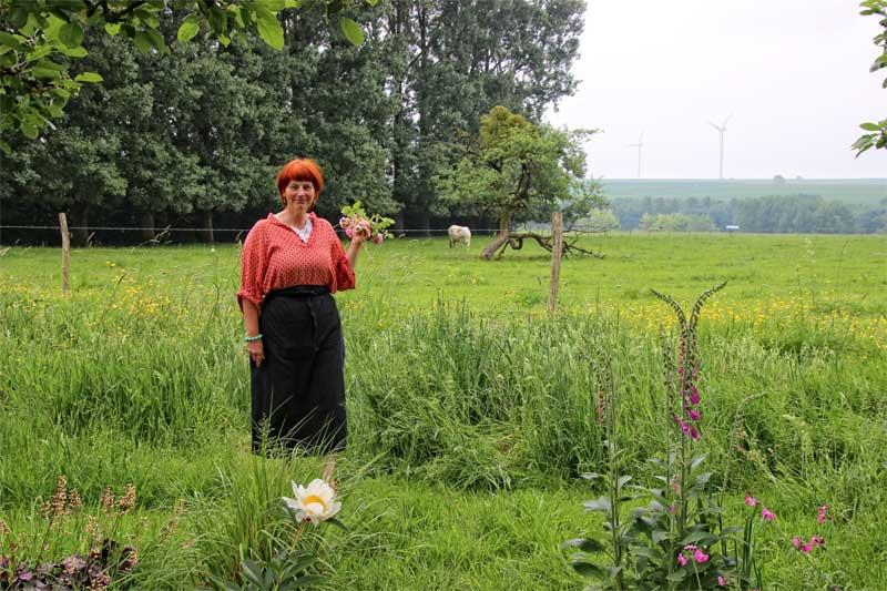 Woman in a large field-liek garden holding bunch of wild flowers