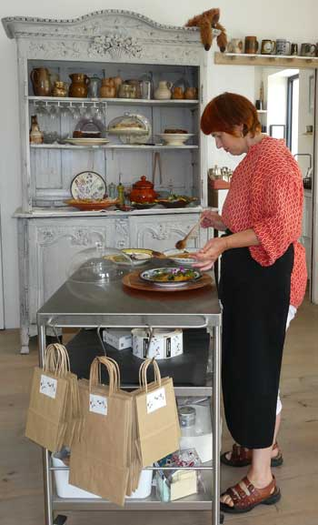 Woman dishes up food in a tiny cafe in her shop in northern France