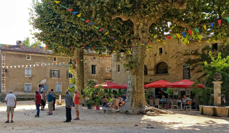 People playing petanque also known as boules, in a town square under plane trees in Labaume Ardeche