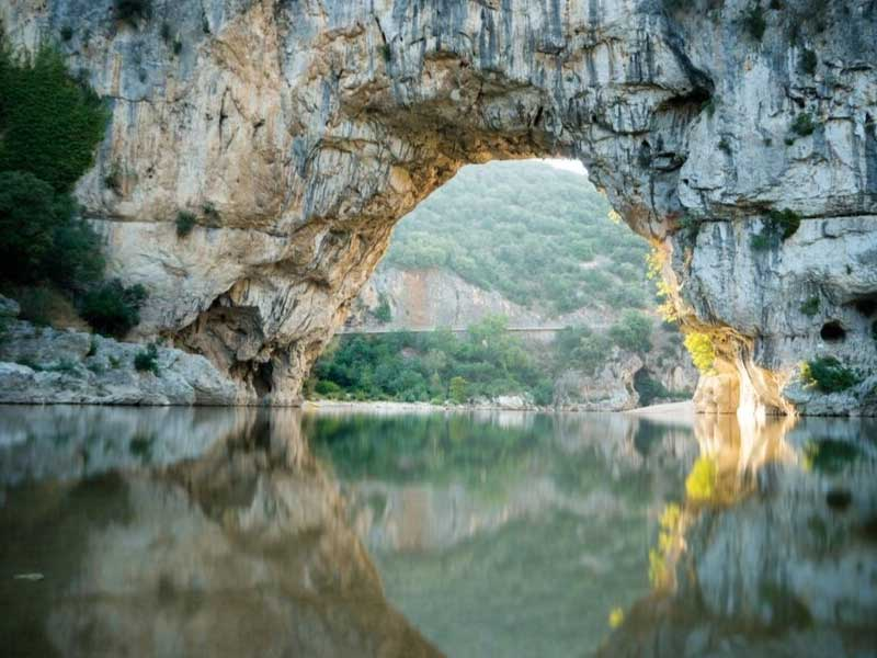 Natural stone bridge carved into rock over the River Ardeche