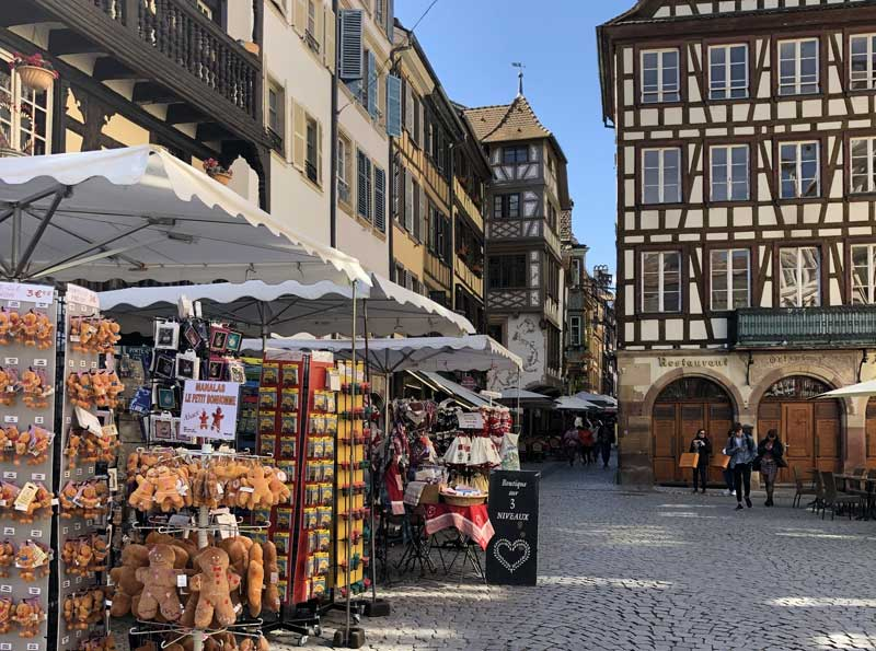 Cobbled street, ancient houses, souvenir shops in Strasbourg, Alsace