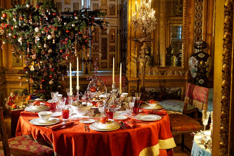 TAble laid for Christmas at the Chateau Vaux le Vicomte, decorations hang from every surface