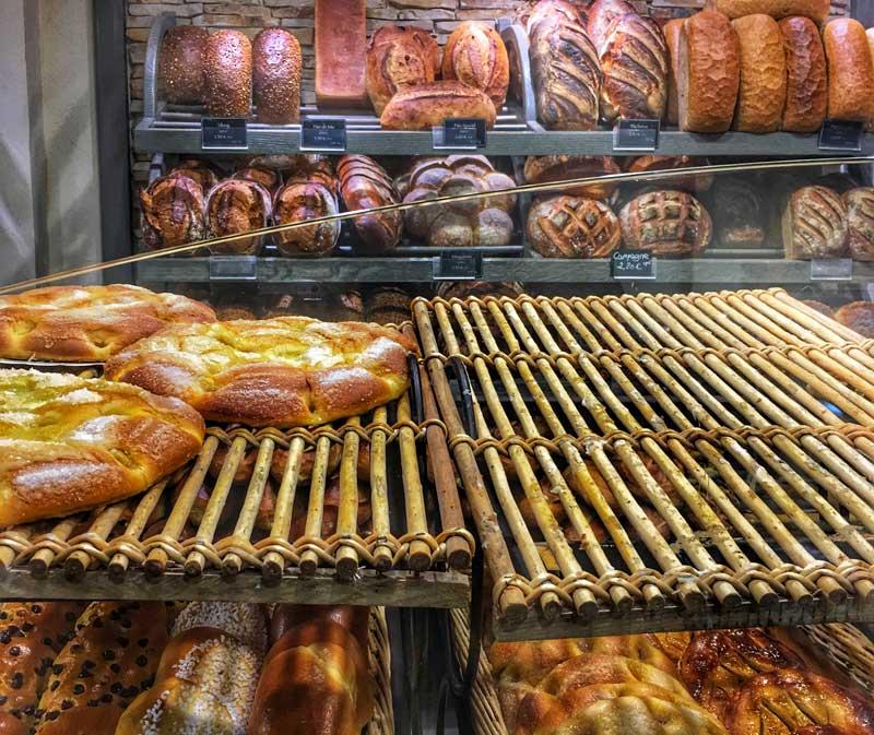 Loaves of bread arranged on shelves in a French bakery
