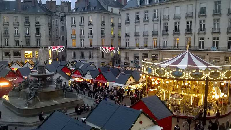 Christmas market of Nantes twinkling lights on chalets in the main square surrounded by tall buildings