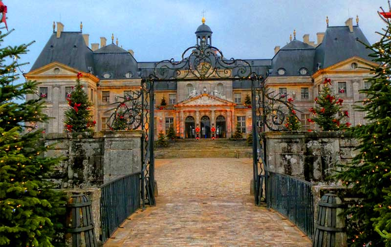 Facade of the Chateau of Vaux-le-Vicomte near Paris with Christmas trees lining the road to the grand doors