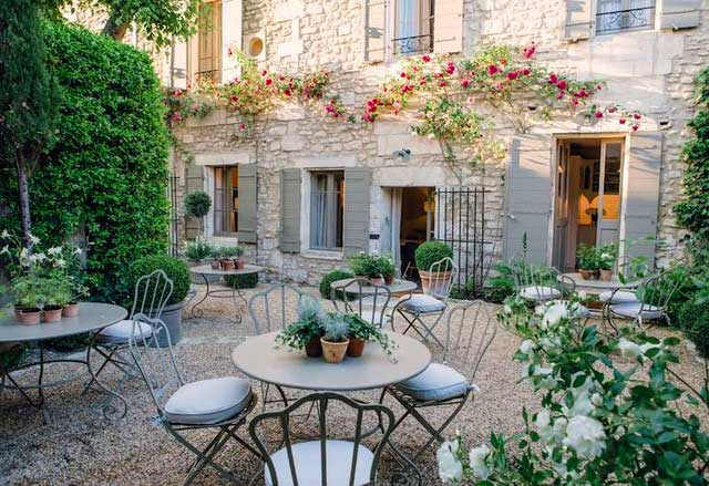 Pretty courtyard of an old manor house, roses growing over the doors, tables and chairs set out