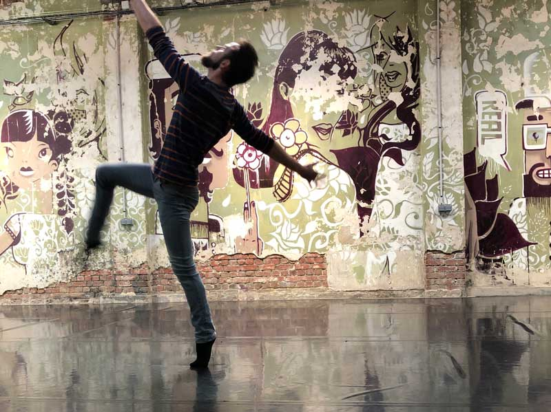 Man dances before a wall of art in Roubaix