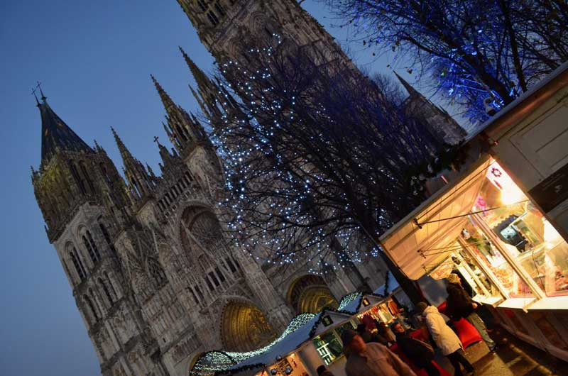 The Cathedral of Rouen looming over the Christmas market, trees with twinkling lights