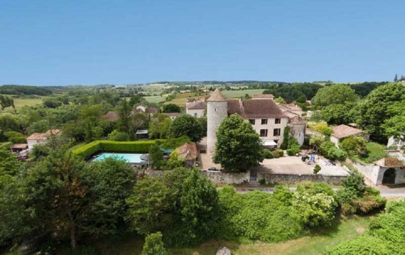 Chateau with a fairy tale like tower surrounded by vineyards and rolling hills in Dordogne