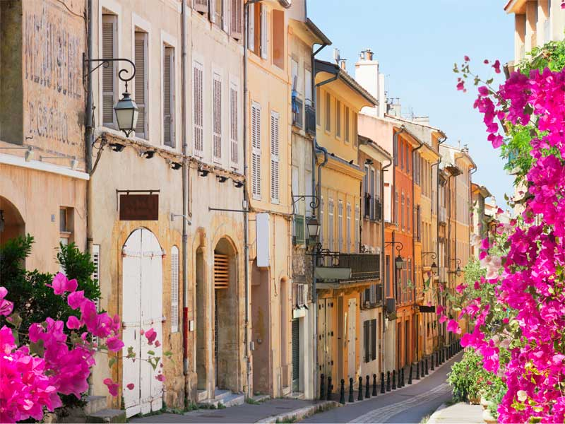 Street lined with old houses with white shutters, ornate lamps and bright flowers in Saint Remy Provence