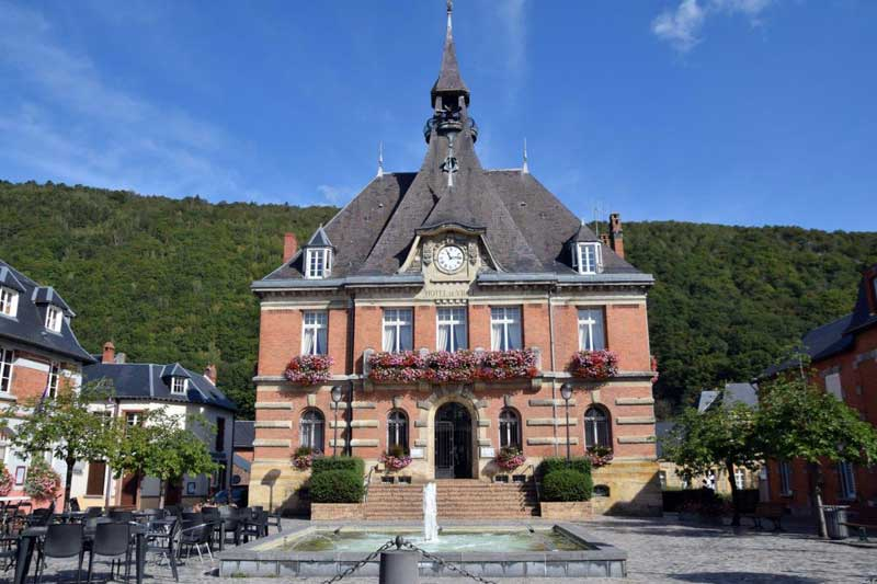 Town Hall of Haybes in Ardennes, flower filled window boxes and forest in background