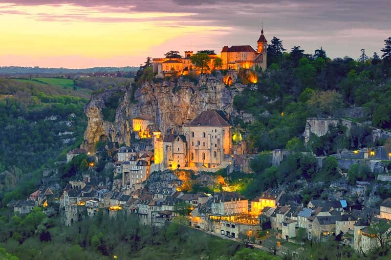 Hill top town of Rocamadour at dusk, houses cliniging to steep cliff sides, Dordogne