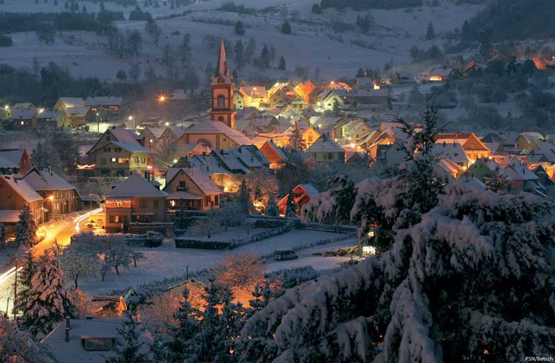 View over a snow covered village at dusk, lights glowing on alpine houses in Alsace