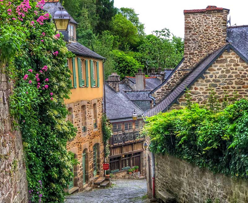 Hilly street in Dinan, Brittany, lined with ancient houses dripping with roses