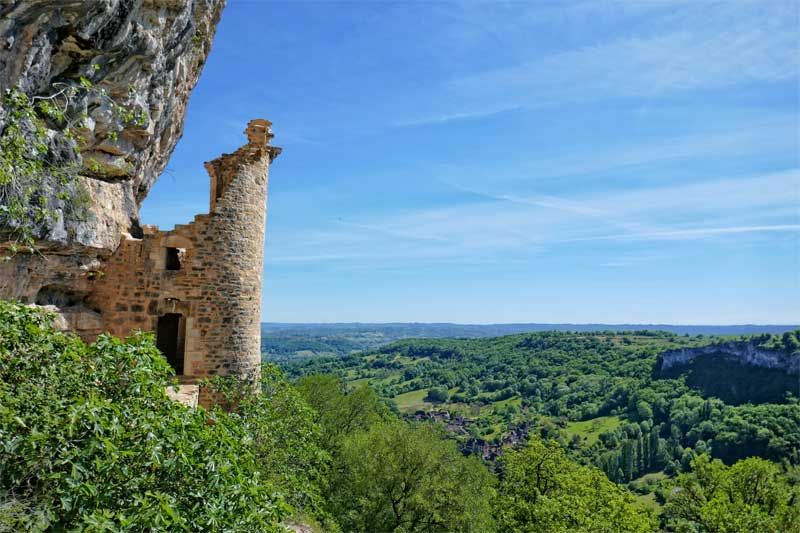 View over the Valley of Dordogne, a ruined chateau juts out of cliff over vineyards and valleys