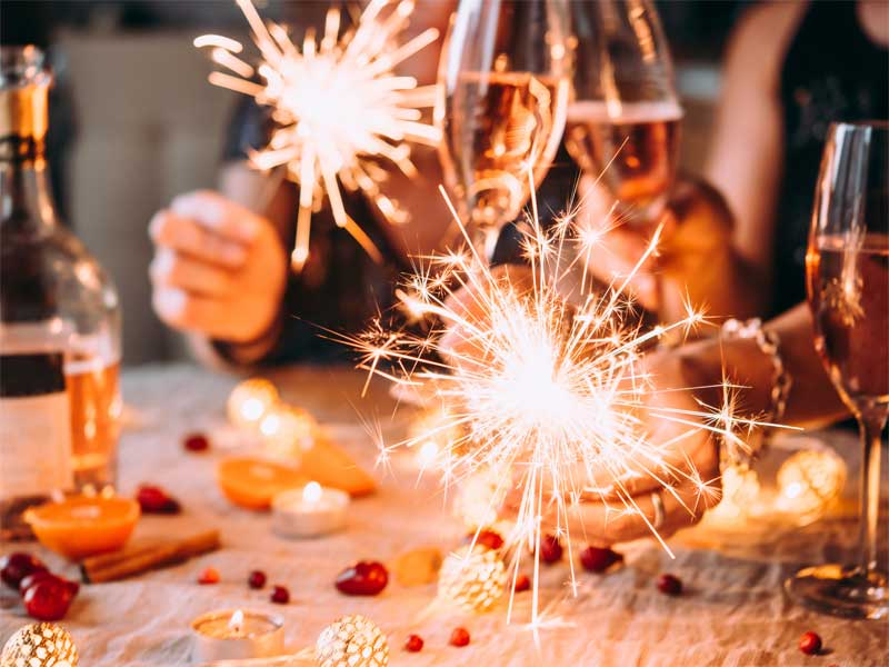People clinking glasses of wine and holding sparklers