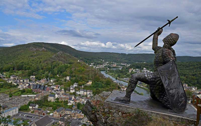 Statue of a knight in chain mail, holding a sword aloft in one hand and looking over the river Meuse
