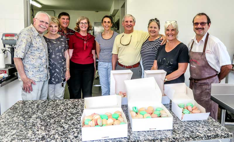 Group of men and women stand before a table with boxes of macarons made in a cooking class in Gers