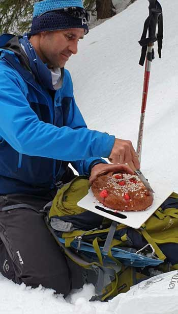 Guide kneeling in the snow to unwrap a cake to share with his guests