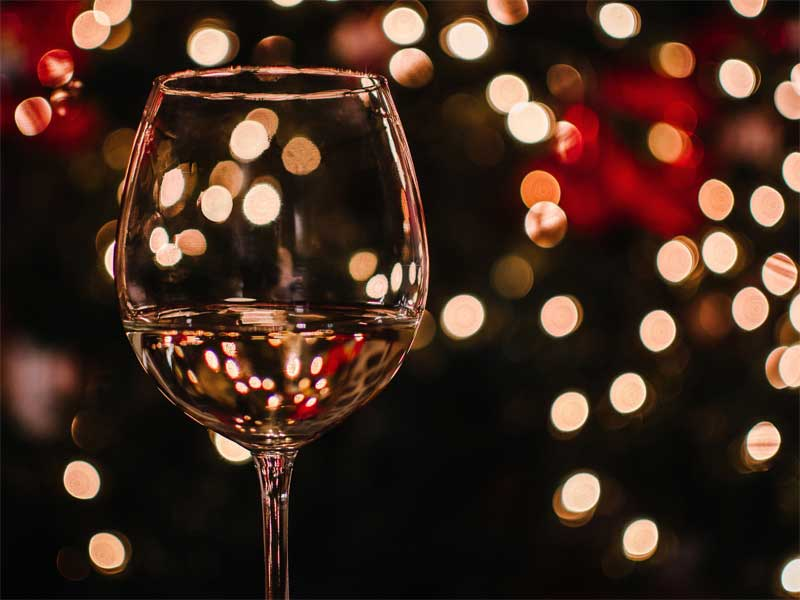 Glass of white wine surrounded by Christmas lights
