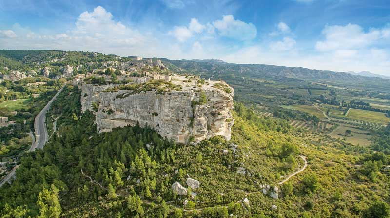 View of Les Alpilles, Provence from the sky, a rocky outcrop in a sea of vineyards and forests