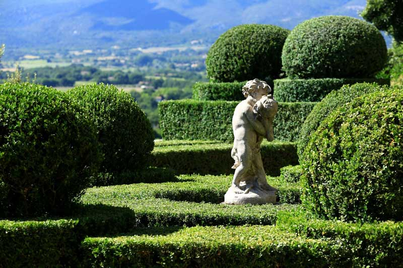 White stone statue in a sea of green topiary in a garden in Ansouis, Provence