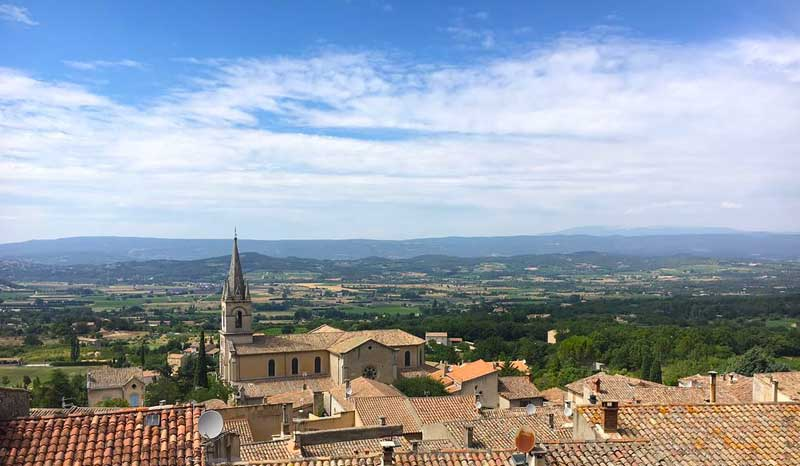 View over the top of the town of Bonnieux, Provence, terracotta tiled roofs against a blue sky