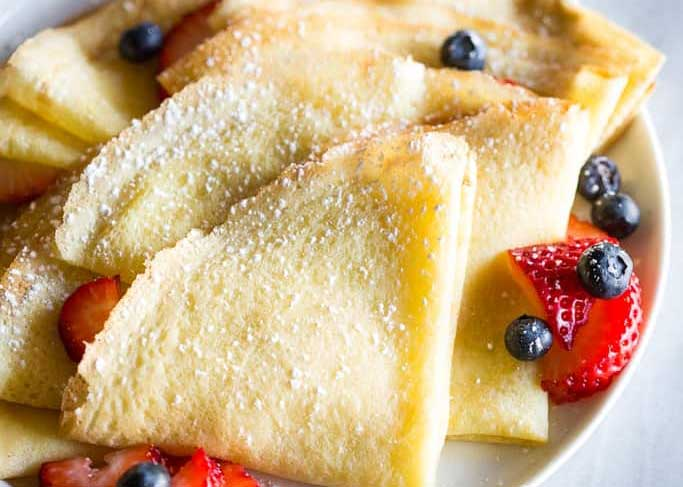 A plate of think French style pancakes with French fruit