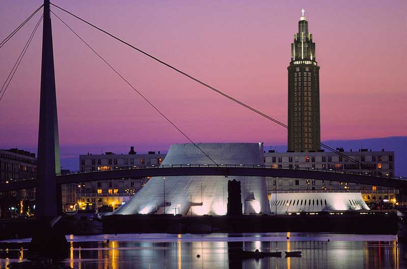 View of Le Havre city at night, architectural landmarks lit up against a dusky purple sky
